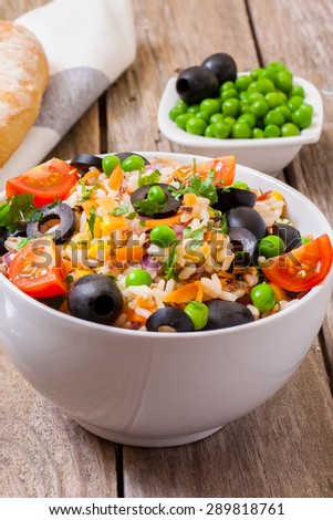 Fresh rice salad in a bowl on wood surface