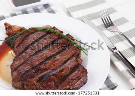 fresh rich juicy grilled beef meat steak fillet entrecote  with marks on white plate over wooden table decorated with sauces and cutlery new york style - stock photo