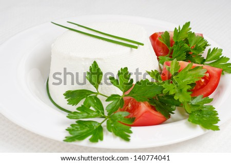 Fresh ricotta cheese with parsley leaves and tomatoes on white table - stock photo