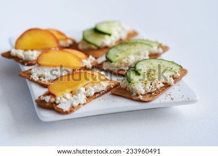 Fresh ricotta cottage cheese snack starter platter appetiser with sliced peach nectarine and cucumber, perfect party canapes - stock photo