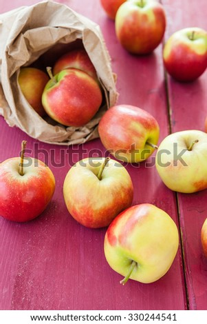 Fresh ripe apples in paper bag on wooden background - stock photo