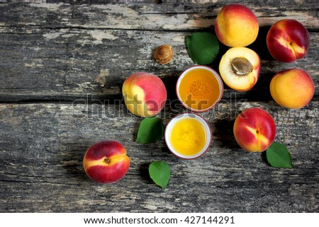 Fresh ripe apricots and apricot oil on old wooden background top view - stock photo