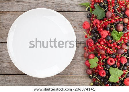 Fresh ripe berries and empty plate on wooden table background with copy space - stock photo