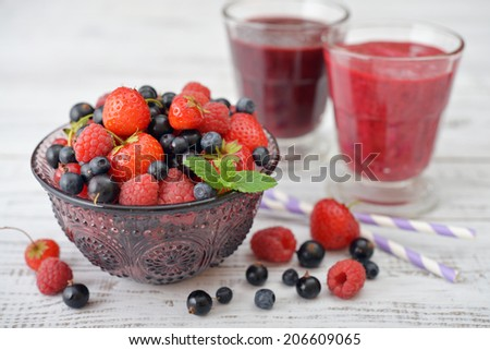 Fresh ripe berries in glass vase with smoothies on light background - stock photo