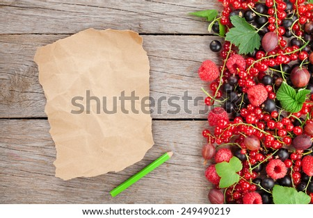 Fresh ripe berries on wooden table background and piece of paper for copy space - stock photo