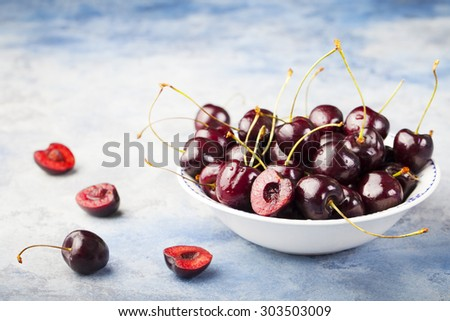 Fresh ripe black cherries in a white bowl on a blue background. copy space - stock photo
