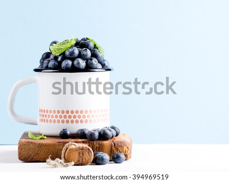 Fresh ripe blueberries in country style enamel mug on rustic wooden board over blue pastel background, selective focus, copy space - stock photo