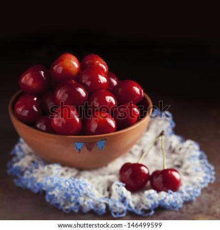 Fresh ripe cherries in a bowl on dark background - stock photo