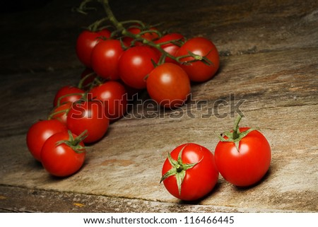 Fresh, ripe cherry tomatoes on an old chopping board. - stock photo