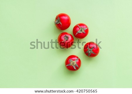 Fresh ripe cherry tomatoes on green background, top view - stock photo