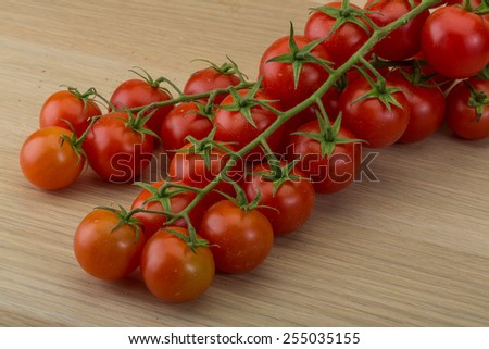 Fresh ripe Cherry tomatoes on the branch - stock photo