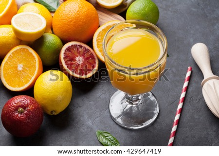 Fresh ripe citruses and juice. Lemons, limes and oranges on dark stone background - stock photo