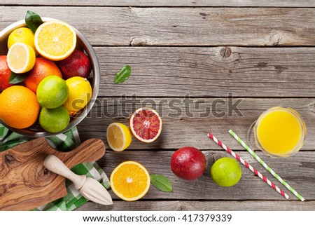 Fresh ripe citruses and juice. Lemons, limes and oranges on wooden background. Top view with copy space - stock photo