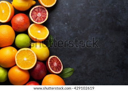Fresh ripe citruses. Lemons, limes and oranges on dark stone background. Top view with copy space - stock photo