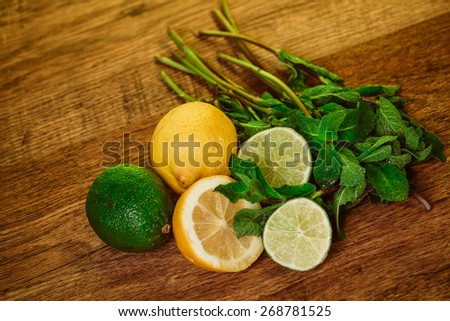 Fresh ripe citruses with mint  on garden wood table - stock photo