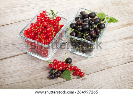 Fresh ripe currant berries on wooden table background - stock photo