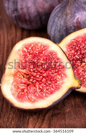 Fresh ripe figs and a half cut on a wooden background closeup