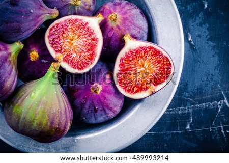 Fresh ripe figs in a bowl closeup on a dark background