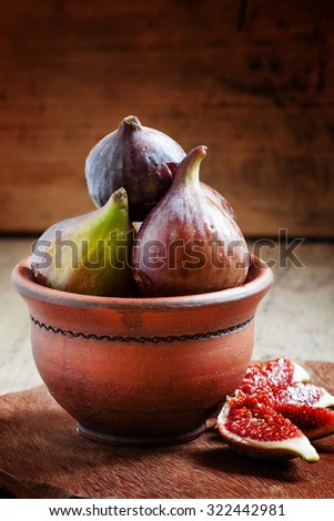 Fresh ripe figs in a clay bowl, selective focus - stock photo