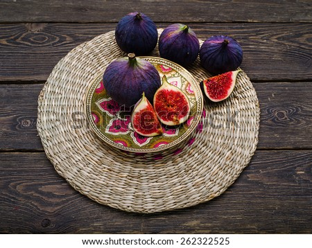 Fresh ripe Figs in blue plate on vintage wooden background - stock photo