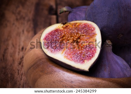 Fresh ripe figs in bowl on wooden table. Close up.