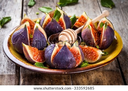 Fresh ripe figs with honey and mint leaves on a rustic wooden table - stock photo