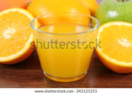 Fresh ripe fruits and glass of juice on wooden surface plank, grapefruit orange apple, healthy lifestyles nutrition and strengthening immunity - stock photo