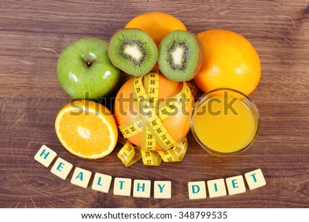 Fresh ripe fruits, glass of juice and tape measure on wooden surface plank, grapefruit orange kiwi apple, healthy lifestyles diet and strengthening immunity - stock photo