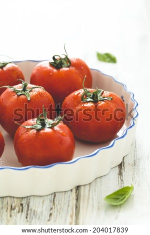 Fresh ripe grape tomatoes inside a white ceramic oven dish on wooden table, rustic style  - stock photo