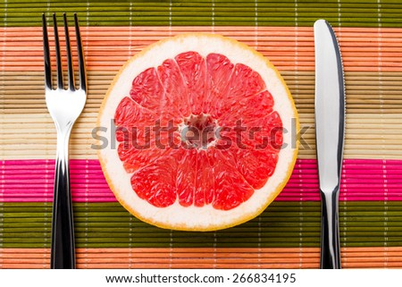 Fresh, ripe grapefruit is lying between fork and knife, symbolizing a healthy eating. Fruit still life - stock photo