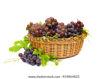 Fresh ripe grapes (Vitis vinifera) with leaves in the basket on a white background - stock photo