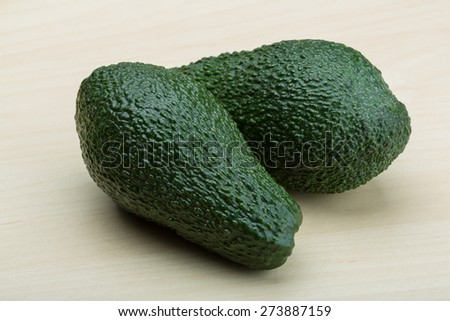 Fresh ripe green avocado on the wood background - stock photo