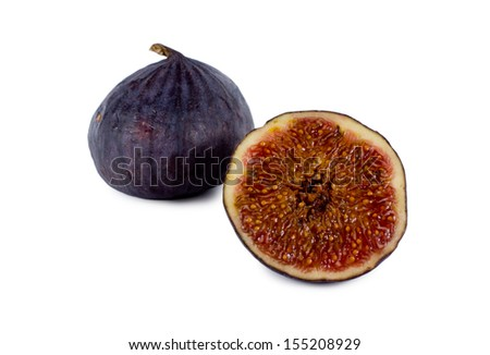 Fresh ripe halved purple fig showing the texture of the sweet succulent pips with a whole fig alongside on a white background - stock photo