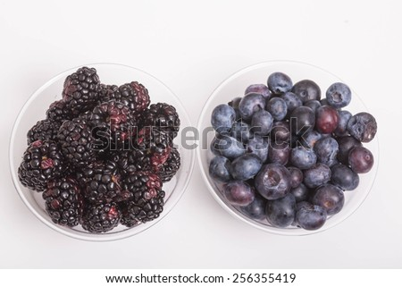 Fresh, ripe, juicy berries in clear cup on a white counter - stock photo