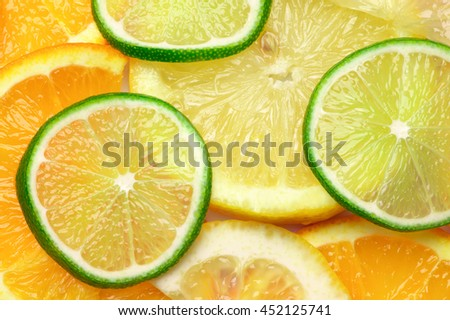 Fresh ripe juicy orange, lime and lemon slices close-up as background. Top view point. - stock photo