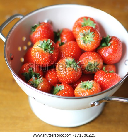 Fresh ripe juicy strawberry harvest or crop in a white colander, selective focus - stock photo