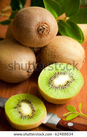 Fresh ripe kiwi with leaves on the wooden table - stock photo