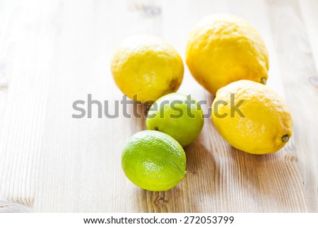 Fresh ripe Lemons and Limes on wooden table - stock photo