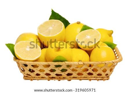 Fresh ripe lemons in wicker basket isolated on white background - stock photo