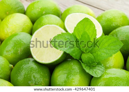 Fresh ripe limes with mint on wooden table - stock photo