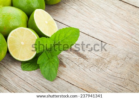 Fresh ripe limes with mint on wooden table with copy space - stock photo
