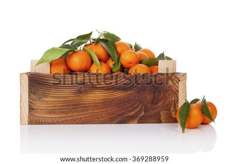 Fresh ripe mandarines with green leaves in wooden crate. Organic fresh mandarines, healthy fruit eating.  - stock photo