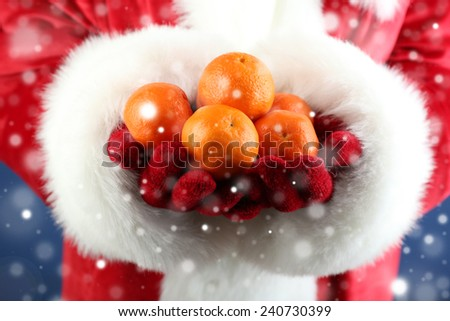 Fresh ripe mandarins in hands, close-up, on blue background - stock photo