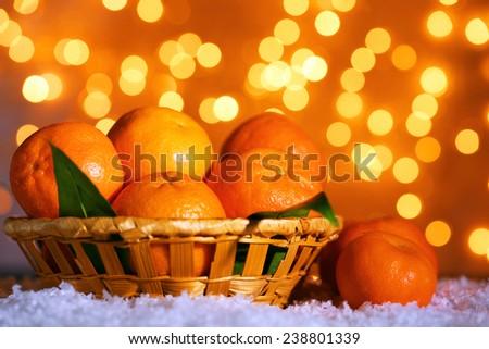 Fresh ripe mandarins on snow, on lights background - stock photo