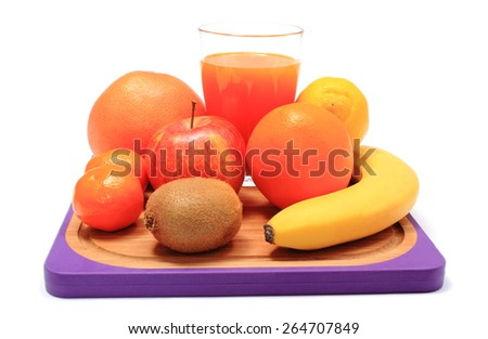 Fresh ripe natural fruits and glass of juice on cutting board, apple, grapefruit, banana, lemon, orange, kiwi, concept for healthy nutrition and strengthening immunity - stock photo
