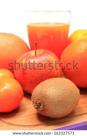 Fresh ripe natural fruits and glass of juice on cutting board, apple, grapefruit, orange, kiwi, concept for healthy nutrition and strengthening immunity - stock photo