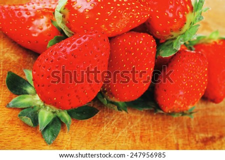 fresh ripe pink strawberry over wooden plate - stock photo