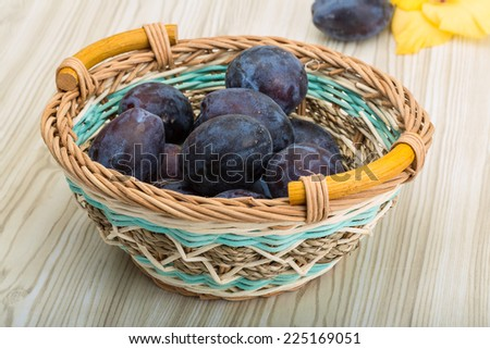 Fresh ripe prunes in the bowl on wooden background