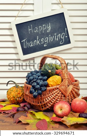 Fresh ripe pumpkins, apples  and grape in wicker basket with chalkboard over wooden background
