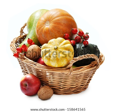 Fresh ripe pumpkins, apples, grape and nuts in wicker basket isolated on white